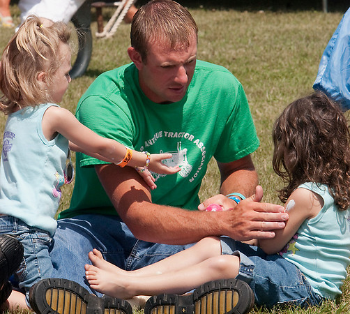Record-Eagle/Douglas Tesner<br /> Justin Hyde applies sun protection to his daughter Makayla, 3, left, and his niece Natalie, 4, as they listen to music at the Suttons Bay Blues Festival.