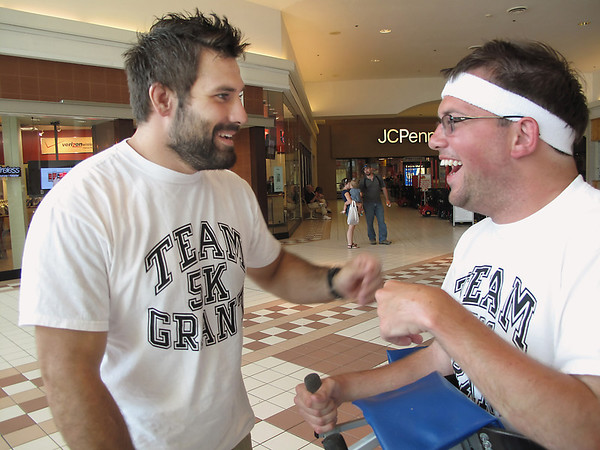 Record-Eagle/Jodee Taylor<br /> Grant Forrester, right, of Traverse City, and Phil Thiel, a friend visiting from Atlanta, share a laugh during a training walk at the Grand Traverse Mall. Forrester, a quadriplegic, plans to walk the 5K in Saturday's Festival of Races, part of the National Cherry Festival.