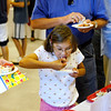 Record-Eagle/Jan-Michael Stump<br /> Elliana Burns, 9, of Reed City samples some of the cherry-themed foods with her mother Polly Burns (cq), left, and father Paul Burns, right, during Friday's Cherry Connection: Bringing Together Festival, Farm and Fruit Friday at the Northwest Michigan Horticultural Research Station operated by Michigan State University.