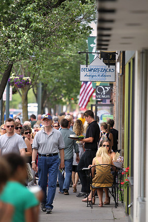 Record-Eagle/Keith King<br /> Pedestrians travel along Front Street through downtown Traverse City on Tuesday during the National Cherry Festival.