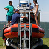 Record-Eagle/Jan-Michael Stump<br /> U.S. Coast Guard Seaman Chris Yaw gives a tour of the guard's 25-foot R.B.S. (Response Boat Small) to twins Jonathon and Jennifer Deeren, 11, at the Open Space during Heroes' Day at the National Cherry Festival.
