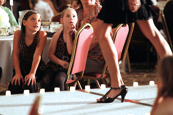 Record-Eagle/Jan-Michael Stump<br /> Alexandra Builes, left, and Olivia Grajewski, both 7, watch models on the runway during the National Cherry Festival Royale Pageant of Fashion Wednesday at the Park Place Dome.