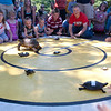 Record-Eagle/Douglas Tesner<br /> Kids pound on the stage to get their turtles moving during the Turtle Races at F&M Park Monday.