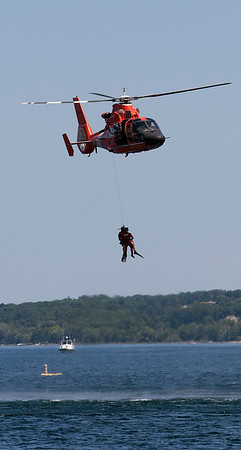 Record-Eagle/Douglas Tesner<br /> A U.S. Coast Guard helicopter from Traverse City puts on a rescue demonstration at the start of the National Cherry Festival air show.