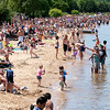Record-Eagle/Douglas Tesner<br /> Hundreds of boats, swimmers and beachgoers jam the shoreline and water near West End Beach opening day of the National Cherry Festival.