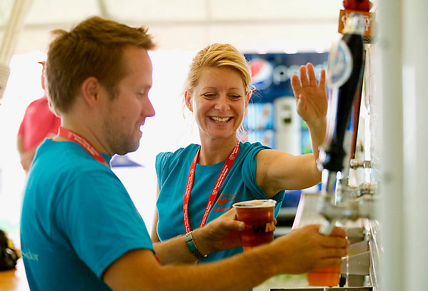 Record-Eagle/Jan-Michael Stump<br /> Aaron Swanker, left, and Heather Bolton pour beers for customers at the beer tent Friday during the National Cherry Festival.