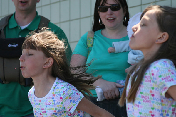 Record-Eagle/Laura Wright<br /> 9-year-old Elliana Rasmussen, left, and her 7-year-old sister Adonia, right, participate in a cherry pit-spit contest, while mom Lora cheers them on.