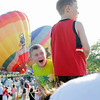 "Record-Eagle/Jan-Michael Stump<br /> ""It's real fire!"" Zeke Bolde, 4, tells his father, John, right, as they and Zak, 7, center, and Zoey, 7 (not pictured) watch hot air balloons launch at the Open Space on Friday evening during the Grand Traverse Balloon Classic, which continues through the weekend. About 25 hot air balloons are in Traverse City for the event, which is being held for the first time."