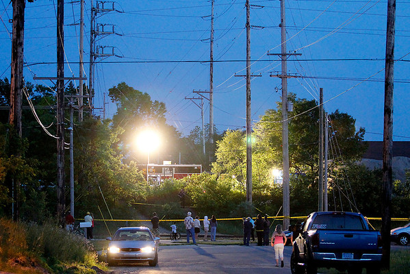 Record-Eagle/Jan-Michael Stump<br /> A crowd gathers along the Tart Trail to watch police investigate the scene where Carly Lewis' body was found Tuesday off Barlow Street. The Traverse City teen had been missing since June 2.