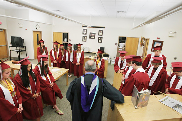 Record-Eagle/Keith King<br /> Traverse City Christian School graduating seniors bow their heads in prayer in the school library prior to the start of the ceremony.