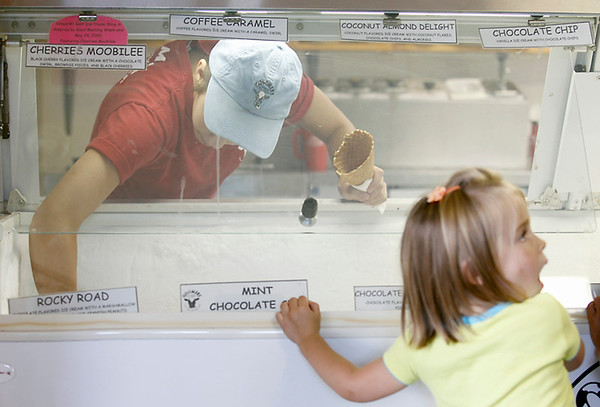 Record-Eagle/Jan-Michael Stump<br /> Kristina Zywicki, 19, prepares an ice cream cone as Lola Rouff, 3, watches at Moomers on Friday afternoon.