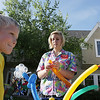 Record-Eagle/Keith King<br /> Camreon Carner, 6, of Lambertville, stands by as Abigail Koprowicz, of Gaylord, a.k.a. Popper the Balloon Twister, forms a balloon tiger during the Alden Thursday Night Stroll.