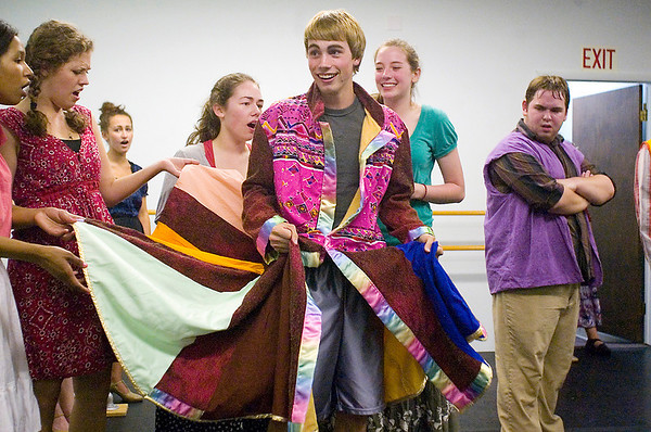 "Record-Eagle/Jan-Michael Stump<br /> Chase Mather (Joseph) tries on his coat with the help of, from left, Rose Kranik, Jessica Elliott, Sarah Lautner and Brianna George during a rehearsal for Miracle Productions' ""Joseph and the Amazing Technicolor Dreamcoat."""
