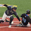 Record-Eagle/ Keith King<br /> Beach Bums catcher Tommy Johnson tags out Windy City's J.T. Restko at home plate during the first game Wednesday night at Wuerfel Park.