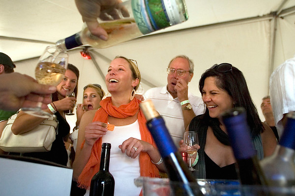 Record-Eagle/Jan-Michael Stump<br /> Lisa Maleski pours a sample from Bel Lago Vineyard and Winery for Lindsey McClintock, left, and Heidi Hageman during Saturday's Leland Wine and Food Festival.