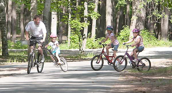 Record-Eagle/Douglas Tesner<br /> John David, of Grand Rapids, and his daughters Lauren, 4, Katelyn, 8, and Ashley, 10, bike through Traverse City State Park.