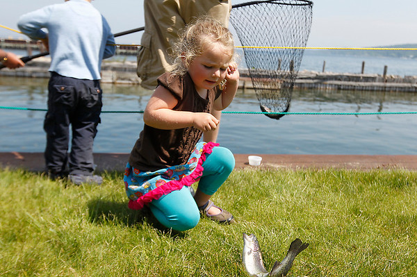 Record-Eagle/Jan-Michael Stump<br /> Izzie Phelps, 4, of Leland, tries to hold onto a rainbow trout caught during Saturday's Kids' Free Fishing Day at the Great Lakes Campus of NMC. About 800 rainbow trout between 12 and 18 inches long were released into a fenced-off harbor for children to catch using provided rods, reels and bait. Volunteers from a number of local groups, including the Traverse City Rotary Club, Grand Traverse Area Sportfishing Association and Michigan Department of Natural Resources, assisted at the event.