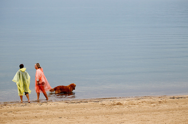 """Record-Eagle/Jan-Michael Stump<br /> Anna Shrift, left, and Abby Shrift play with their dog, Tug, at Clinch Park Beach on a rainy Wednesday afternoon. """"We were going to go swimming, but it got nasty so we bought ponchos,"""" said Anna."""