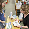 Record-Eagle/ Keith King<br /> Newbery-winning author Lynne Rae Perkins, right, of Suttons Bay, signs copies of her books Friday at Horizon Books for Gabbie Rae Ammond, 12, of Traverse City.
