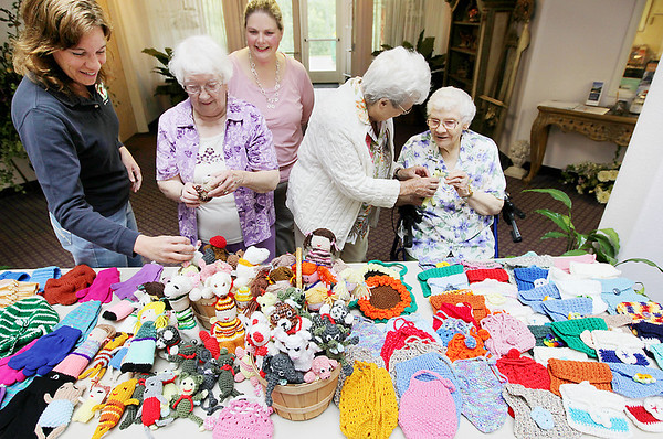 Record-Eagle/Keith King<br /> An assortment of crocheted and knitted items to be donated to Operation Christmas Child lie on a table Tuesday at Glen Eagle senior community. Looking at the collection are, left to right: Dianna DeYoung, area coordinator for Operation Christmas Child; Glen Eagle senior community resident Lori Urch; April Putman, enrichment coordinator at Glen Eagle; Glen Eagle resident Valerie Jewitt; and Glen Eagle resident Gretchen Weeks. Residents of the facility participated in a variety of ways, from fundraising to item creation. Shoeboxes containing the knitted and crocheted items, along with personal care items and school supplies, will be sent to needy children around the world.