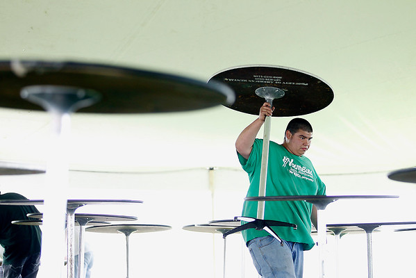 Record-Eagle/Jan-Michael Stump<br /> Nick Ortega sets up tables in the beer tent at the Open Space for next week's National Cherry Festival.