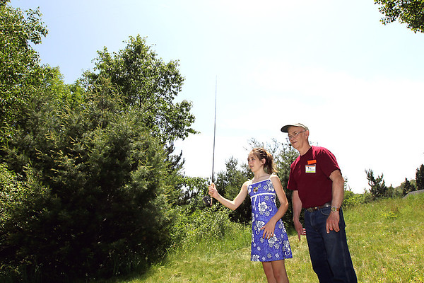 Record-Eagle/Keith King<br /> Rhandi Perry, 12, of Kingsley, is taught how to cast a fly-fishing rod by Bob Summers, who makes fly-fishing rods, and donated a rod he built as a raffle prize with proceeds going toward restoration of the Boardman River.