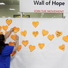Record-Eagle/ Keith King<br /> Ruth Jarvis, on right, alongside her sister, Mikala Coyne, both of Traverse City, places a paper heart on the Wall of Hope. The paper heart was for their mother who has had multiple sclerosis for the last eight years.