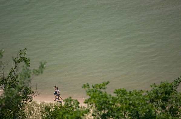 Record-Eagle/Jan-Michael Stump<br /> Runners make their way along the Lake Michigan shoreline near the Arcadia Bluffs.