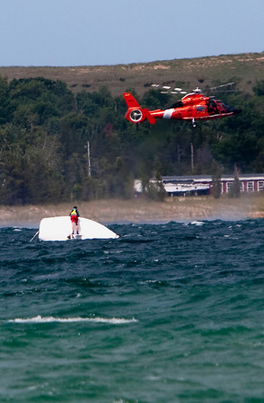 Record-Eagle/Douglas Tesner<br /> A United States Coast Guard helicopter from Air Station Traverse City hovers near an overturned boat in Sleeping Bear Bay Friday morning.