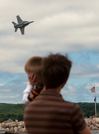 Record-Eagle/Douglas Tesner<br /> Gavin Graetz, 2, covers his ears as his father, Grey Graetz, holds him as a U.S. Navy  F-18 Super Hornet flies by during a practice air show Friday for the  National Cherry Festival.