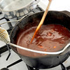 Record-Eagle/Jan-Michael Stump<br /> Derek Robinson stirs a batch of his mahogany red sauce in his Suttons Bay home.