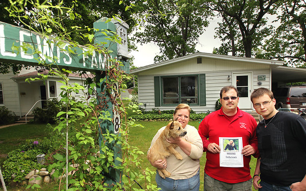 Record-Eagle/Keith King<br /> Carly Lewis' family - from left, mother Susie Lewis, father Todd Lewis, and brother Mitchell Lewis, 18, - in their yard Thursday in Traverse City. Carly Lewis has been missing since June 2.