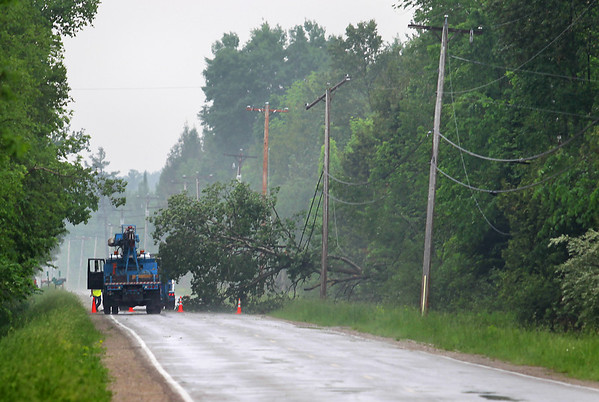 Record-Eagle/Keith King<br /> A Consumers Energy truck parks along County Road 633 in Suttons Bay near a tree that fell on power lines Wednesday.