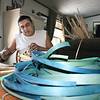 Record-Eagle/Loraine Anderson<br /> Frank Weese weaves a basket at his dining room table surrounded by dyed and natural strips of black ash. A large basket takes him about 48 hours over several days to complete, from cutting the tree and prepping wood strips through weaving.