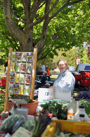 Record-Eagle/Vanessa McCray<br /> Ann Dougherty, president of Learn Great Foods, visits the farm market at The Village at Grand Traverse Commons in late May to tell marketgoers about culinary tours offered by the company.
