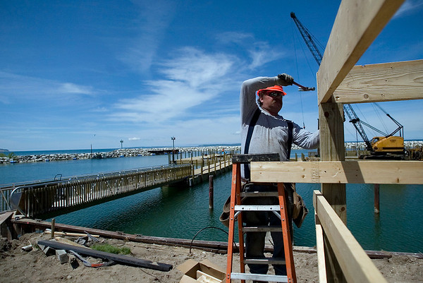 Record-Eagle/Jan-Michael Stump<br /> Dan Sohasky, of DeVere Construction, works on the covered deck of the new boater services building, part of the renovated Leland Harbor. The $3 million project is set to open June 26 with the boater services building opening July 10.