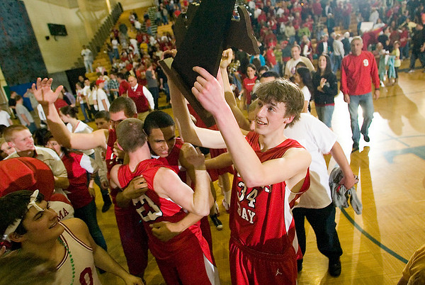 Record-Eagle/Jan-Michael Stump<br /> Suttons Bay's Chase Palmer (34) holds up the regional trophy as Noah Reyhl (23) and Dwuan Anderson (22) celebrate their win over Mason County Central.