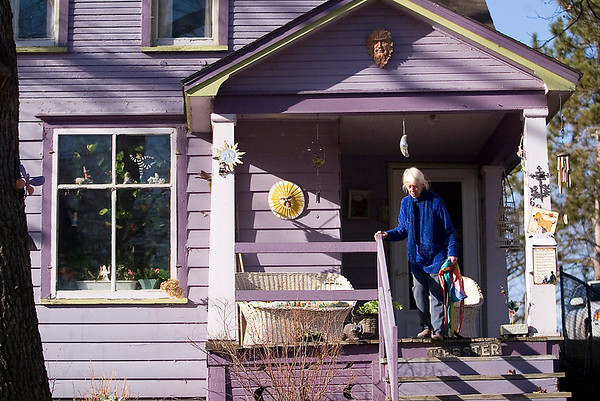 "Record-Eagle/Jan-Michael Stump<br /> Chris Morey outside her Webster Street home on a sunny Monday afternoon. ""It's my obligation to amuse the neighborhood,"" she said of the colorful decorations on her purple home."