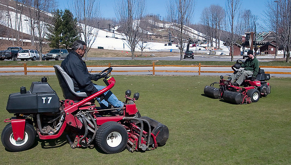 Record-Eagle/Douglas Tesner<br /> With snow-covered ski slopes in the background grounds keepers Wayne York, left, and Dave Dixon work on a practice green at Crystal Mountain Resort & Spa.