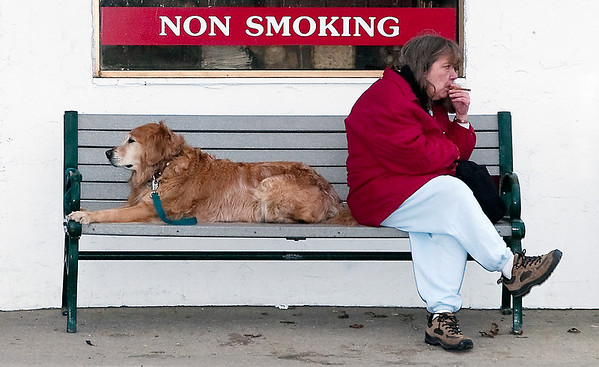 Record-Eagle/Douglas Tesner<br /> Nancy Larson shares a bench outside of J&S Hamburg on Front Street with Oso, a 10 year old Golden Retriever owned by Andrew MacKenzie. According to MacKenzie, each Saturday the dog sits on the bench with others as he eats breakfast inside.