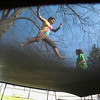 Record-Eagle/Jan-Michael Stump<br /> Isabell Astor, 13, left, and Mikayla Clark, 14, play on the trampoline at Clark's Sixth Street home on Thursday morning. The trampoline usually doesn't come out until after Clark's grandfather's birthday on April 15, but the recent warm weather allowed for an early start. Thursday's temperature reached around 80 degrees, with a similar high forecast today.