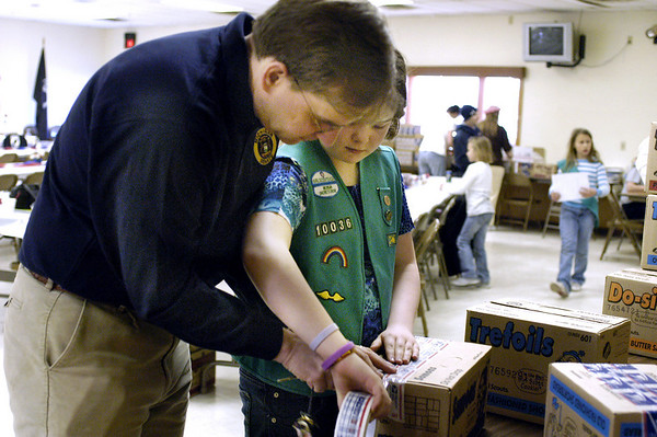 Record-Eagle/Lisa Perkins<br /> State Senator Jason Allen helps his daughter Meredith pack Girl Scout cookies to be sent to soldiers in Iraq.