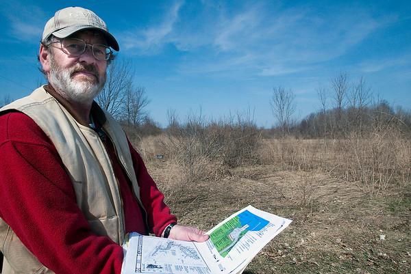 Record-Eagle/Douglas Tesner<br /> Edward Hoogterp holds plans and drawings of what will be the DNR boat launch on Crystal Lake as he stand near what will be the parking lot for the site.