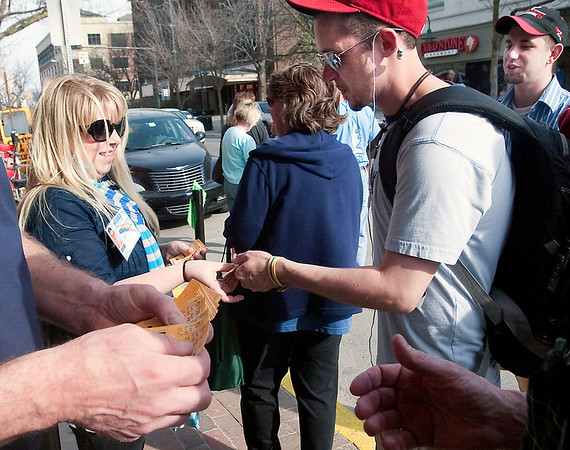 Record-Eagle/Douglas Tesner<br /> Susan Borke hands out free tickets to Vincent Ryan in front of the State Theatre for Saturday's Final four game between Michigan State and Butler. The theatre will be showing the game on the big screen.