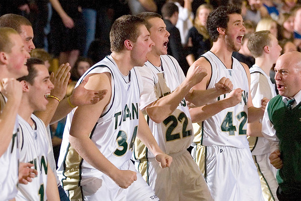 Record-Eagle/Jan-Michael Stump<br /> Traverse City West players Julius Moss (43), Trevor Tooley (22) and Jack Flynn (42), and coach Brett Graham cheer at the end of Wednesday's district playoff win over Traverse City Central.