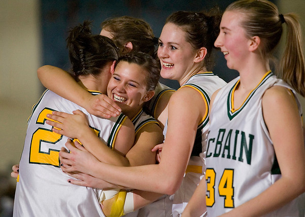 Record-Eagle/Jan-Michael Stump<br /> McBain's Macy Vanderhoef (24) and Annemarie Hamlet (10) celebrate with teammates their win over Kalkaska in Thursday's regional playoff game.
