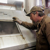 Record-Eagle/Douglas Tesner<br /> Jim Olds checks on sap running through an evaporator at the maple syrup production facility at the Olds Brothers Farm south of Kingsley. Syrup production at the farm started last week.