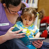 Record-Eagle/Jan-Michael Stump<br /> Katie Ritola and her daughter Lilly, 9 months, read along with assistant librarian Sharon Siladke leads Friday's Baby Play Time at the Interlochen Library.