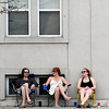 """Record-Eagle/Jan-Michael Stump<br /> Brendan Mcnamara, left, Sara Cnossen, center, and Stacy Smith hang out outside Mcnamara and Cnossens apartment building on Union Street on Monday as temperatures again crack 80 degrees. """"This is our stoop,"""" said Cnossen. """"Our stoop is just a sidewalk,"""" added Smith."""