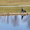 Record-Eagle/Jan-Michael Stump<br /> Dave Gruman, of Suttons Bay, walks along a water hazard at Elmbrook Golf Course in East Bay Township as temperatures climb into the 70s. The course opened its front nine holes Thursday afternoon, and hopes to open the back nine Saturday morning.